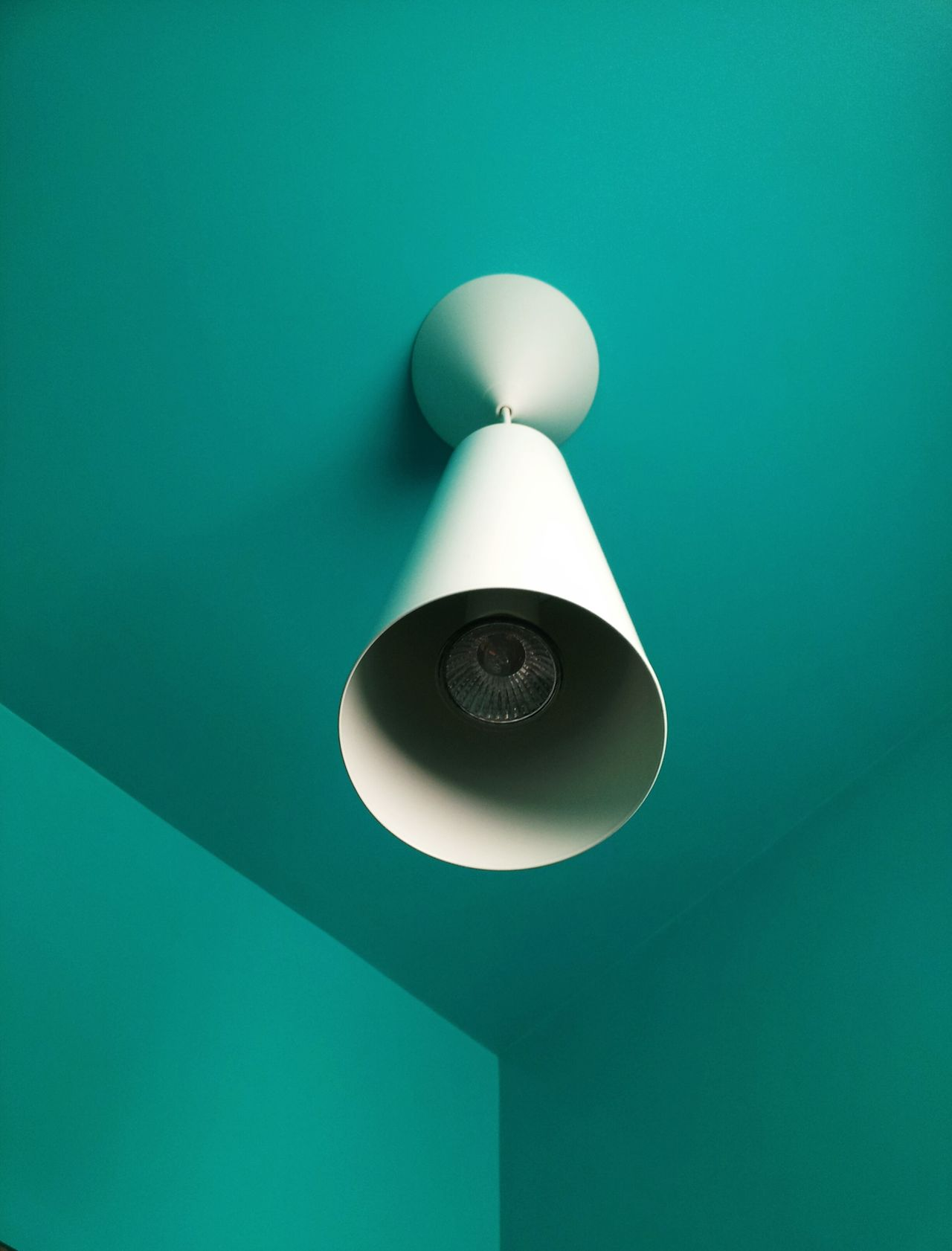 Low angle view of hanging light at turquoise colored ceiling