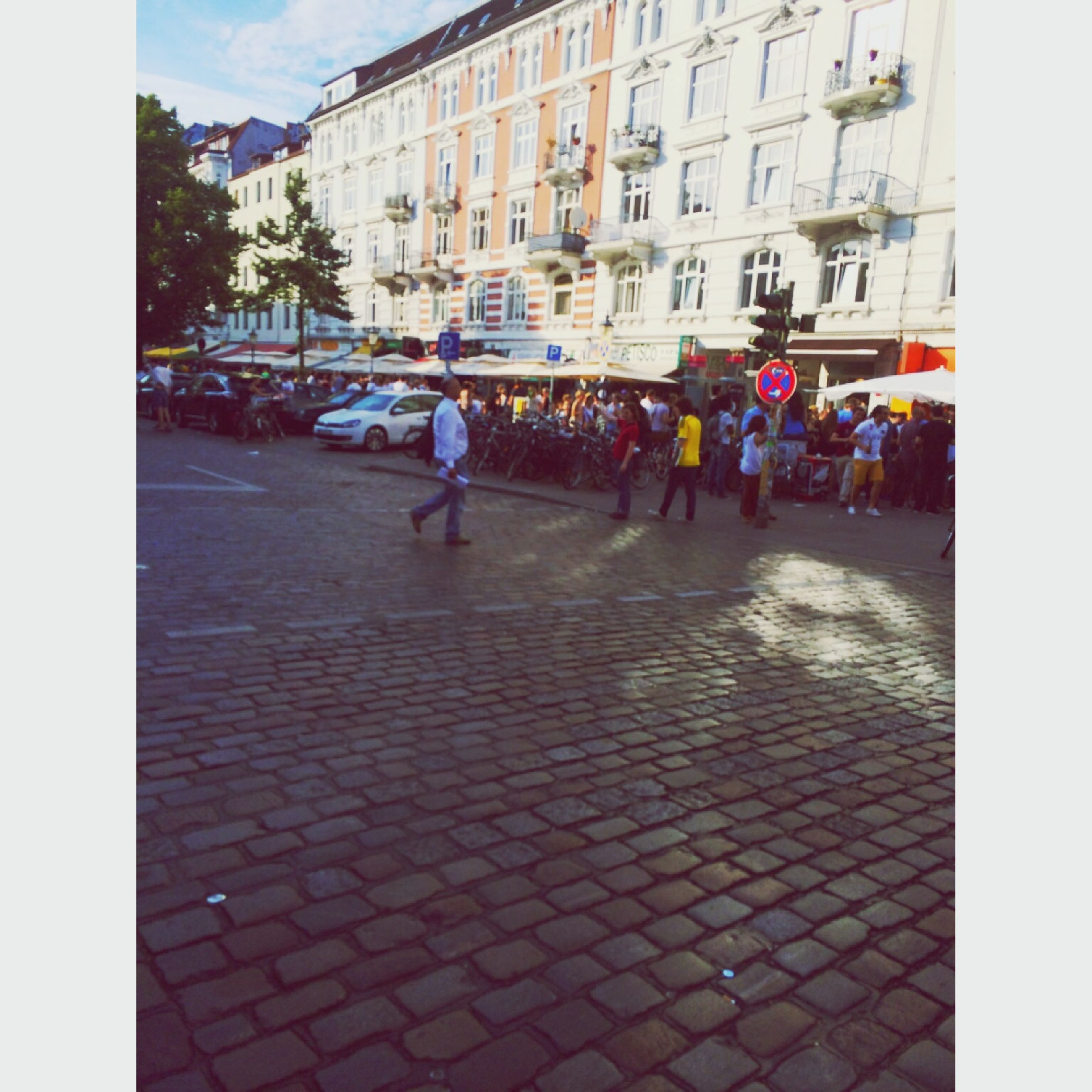 building exterior, architecture, transfer print, built structure, street, city, walking, men, lifestyles, person, city life, auto post production filter, leisure activity, large group of people, full length, cobblestone, rear view, city street, umbrella
