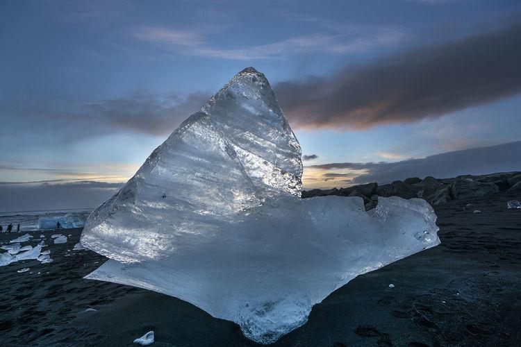 Iceberg on sand at beach against sky during sunset