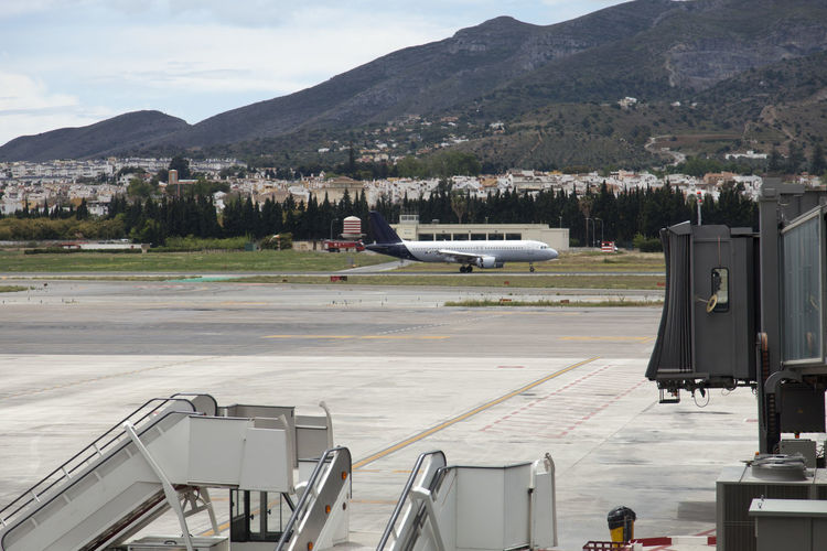 Airplane on runway against mountains