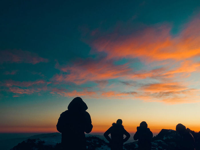 Silhouette people standing by hills against sky during sunset