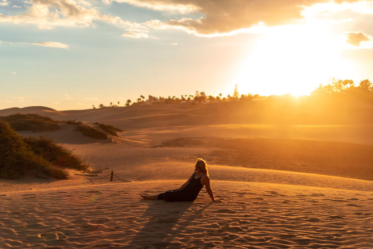 Full length of woman sitting on sand against sky during sunset