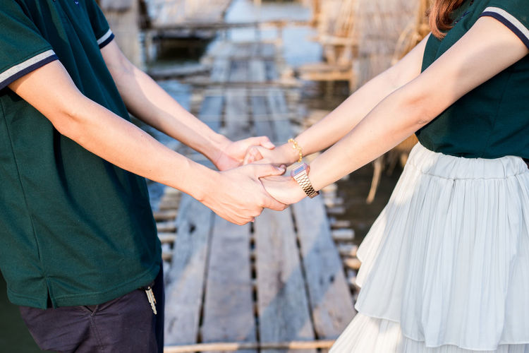 Midsection of couple holding hands on pier