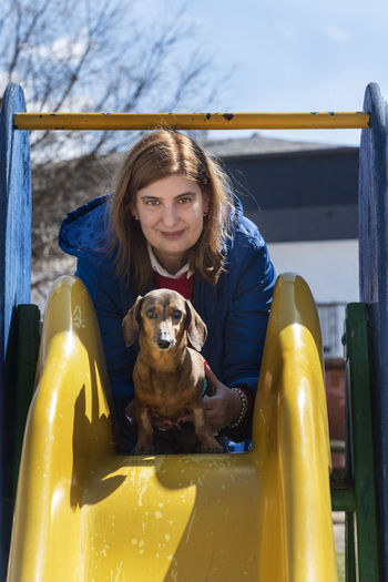 Beautiful woman with her dachshund at the park. Animal lovers concept. Domestic Animals Domestic Pets One Animal Dog Canine Mammal Portrait One Person Looking At Camera Real People Smiling Pet Owner Outside Outdoors Care Background Wallpaper Copy Space Summer Yellow Blue Toboggan Sunny Day Cute Woman People Attractive Breed Pedigree Standard Caucasian Beauty Beautiful Park Dauchshund