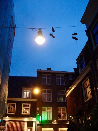 Illuminated Building Exterior Low Angle View Street Light Architecture Lighting Equipment Electricity  Night No People Outdoors Cable Tennis Shoes Shoes On A Wire Hanging Shoes