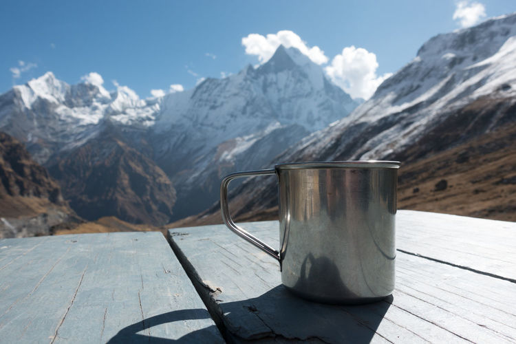 Close-up of mug on table against snowcapped mountains