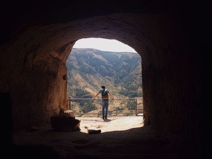 Rear View Of Teenage Boy Standing Against Mountain Seen Through Archway
