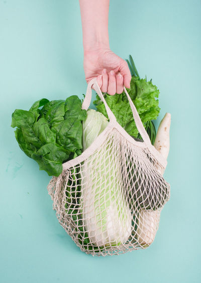 Cropped hand of person holding vegetable basket against blue background