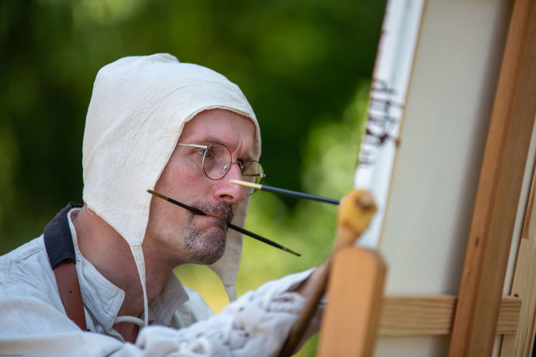 Close-up of man painting on canvas