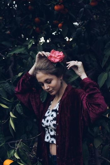 Smiling young woman standing by flowers