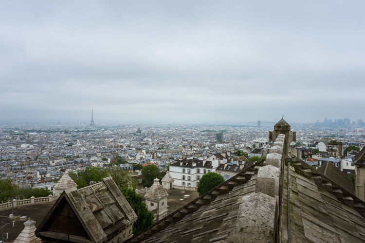 High angle view of city buildings against cloudy sky in paris, france