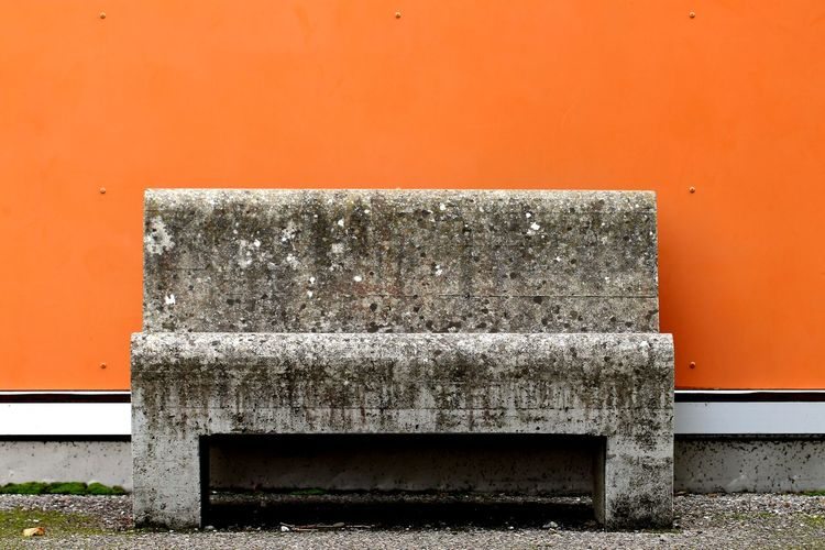 Close-up of old building against orange wall