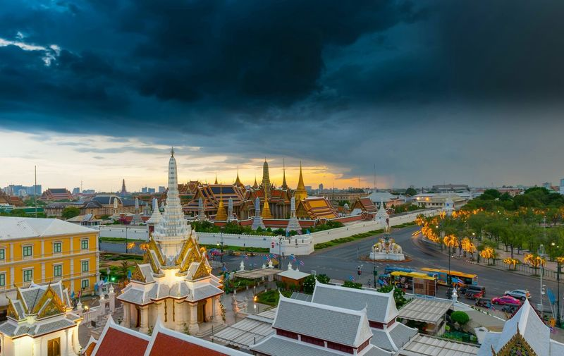 Grand palace and wat phra keaw against cloudy sky during sunset