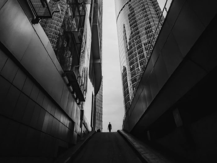 Low angle view of people walking on footpath amidst buildings