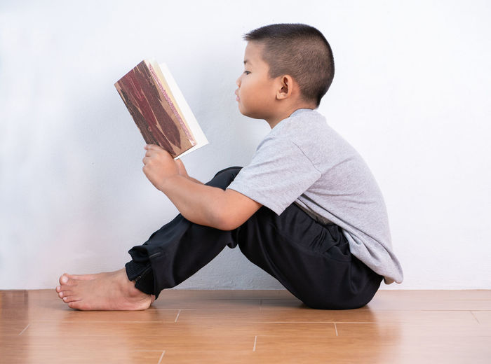 Side view of boy sitting on wooden floor against wall