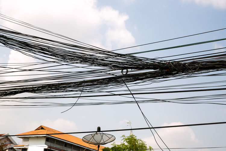 Low angle view of power lines and building against sky