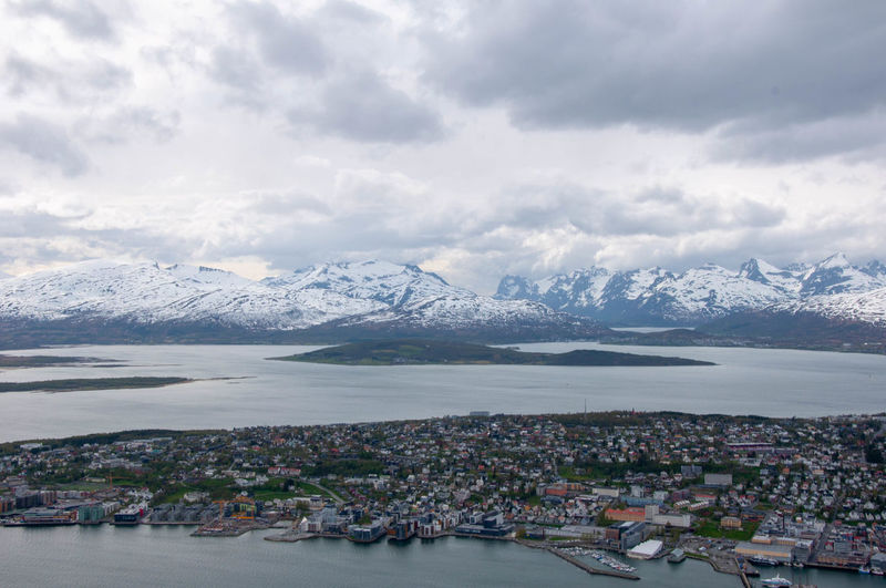 Aerial view of townscape by snowcapped mountains against sky