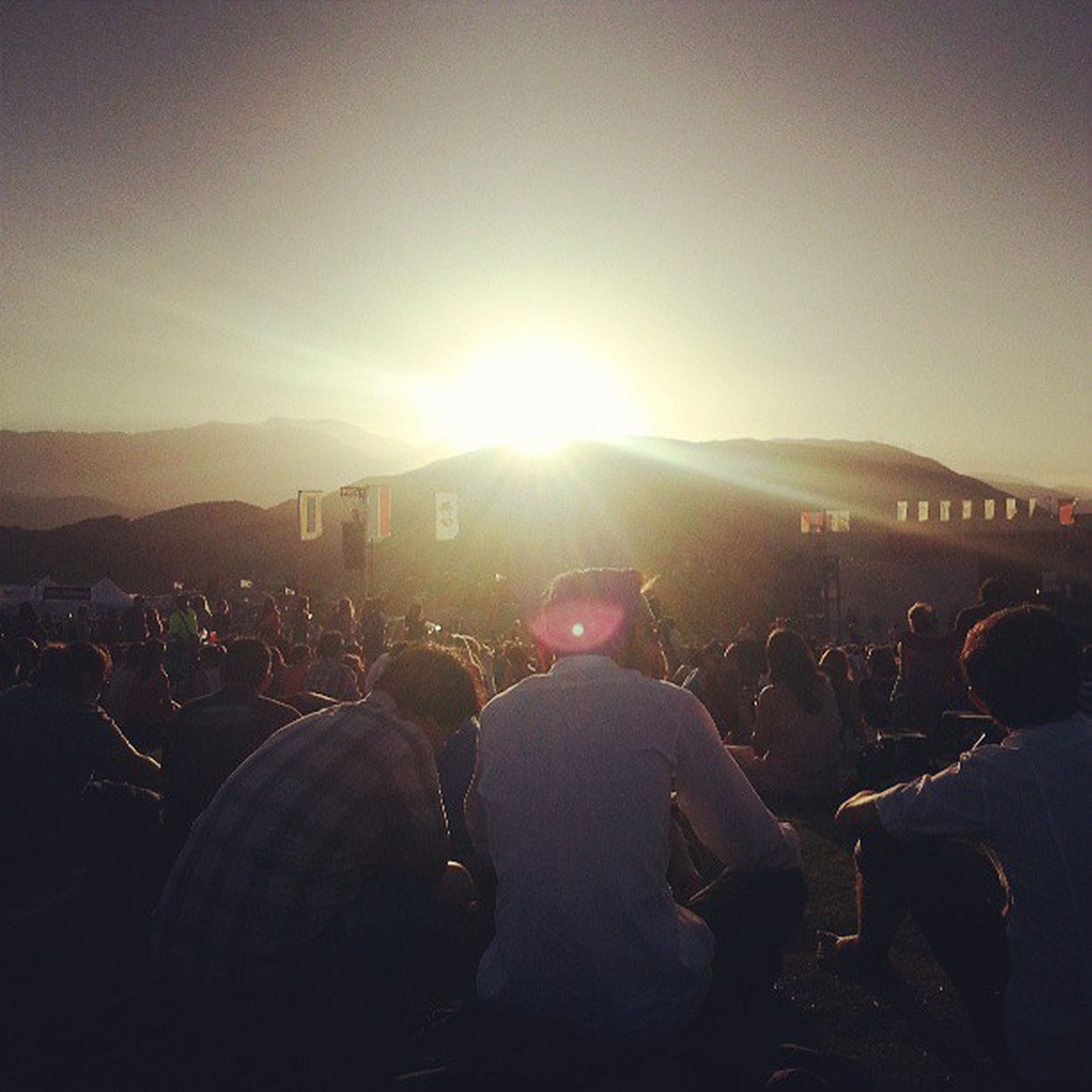 lifestyles, leisure activity, men, large group of people, sun, sunset, person, lens flare, sky, crowd, sunbeam, clear sky, rear view, sunlight, togetherness, city, silhouette, standing