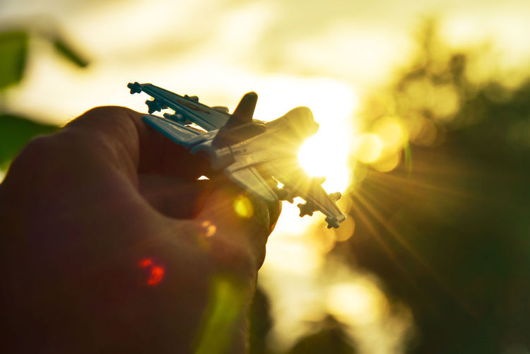 Dreams In To The Sky Air Plane Close-up Day Gold Light Gun Handgun Holding Human Body Part Human Hand One Person Outdoors People Real People Sky Sunset Toy Weapon