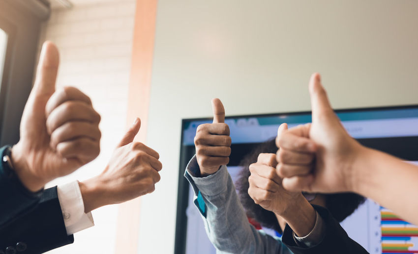 Business team with thumbs up sign at office