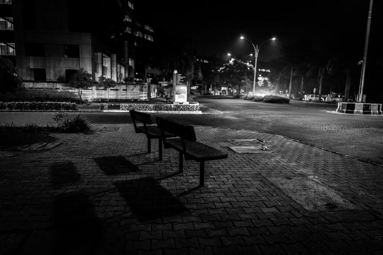 Empty chairs and tables in street at night