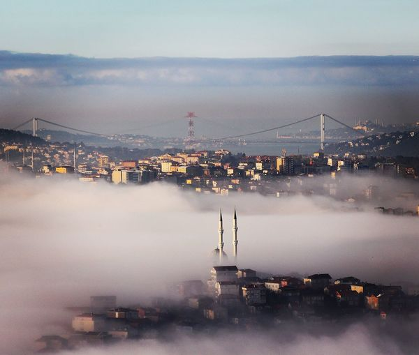 City under foggy weather against sky