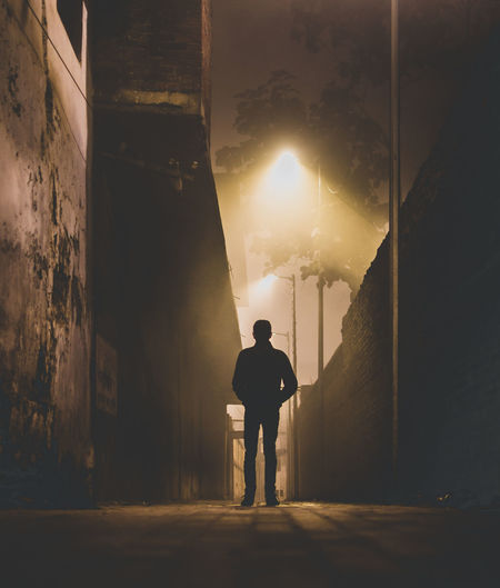 Rear view of silhouette man standing by illuminated buildings in city