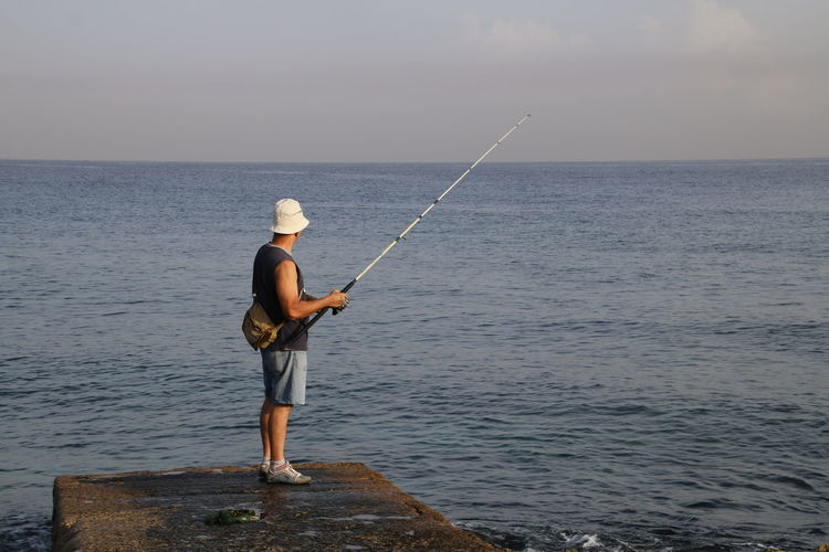 Man fishing on concrete jetty in sea against sky