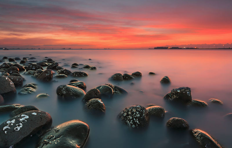 Scenic View Of Rocks In Sea Against Sky At Sunset