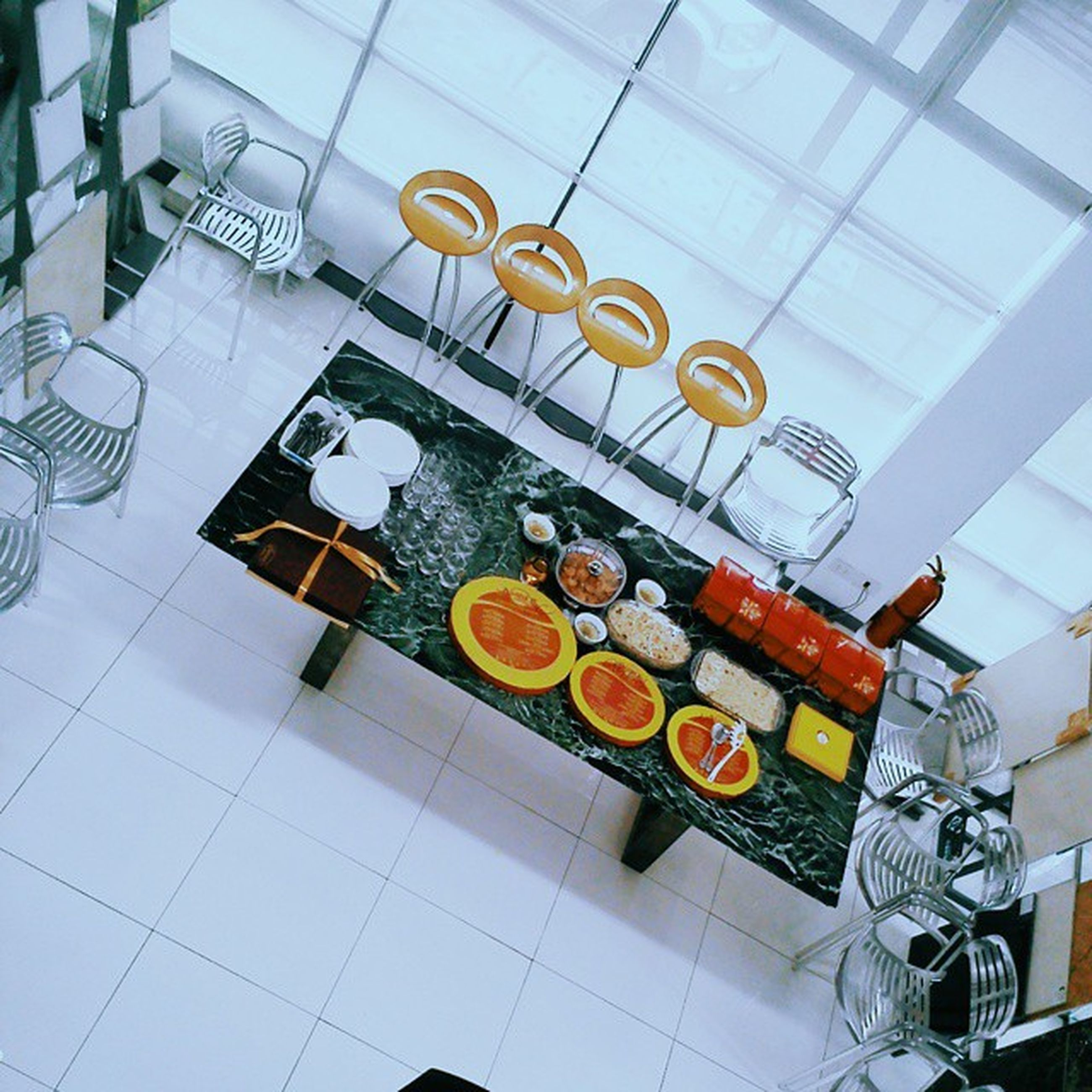 indoors, high angle view, variation, large group of objects, arrangement, hanging, table, tiled floor, glass - material, day, no people, low angle view, still life, reflection, ceiling, food and drink, abundance, choice, tile, directly above