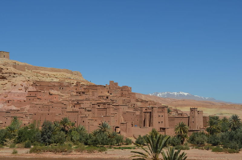 Ait-Ben-Haddou Ancient Ancient Civilization Architecture Arid Climate Beauty In Nature Blue Clear Sky Day Desert History Landscape Mountain Mountain Range Nature No People Outdoors Plant Rock - Object Scenics Sky Tourism Tranquil Scene Travel Destinations Tree