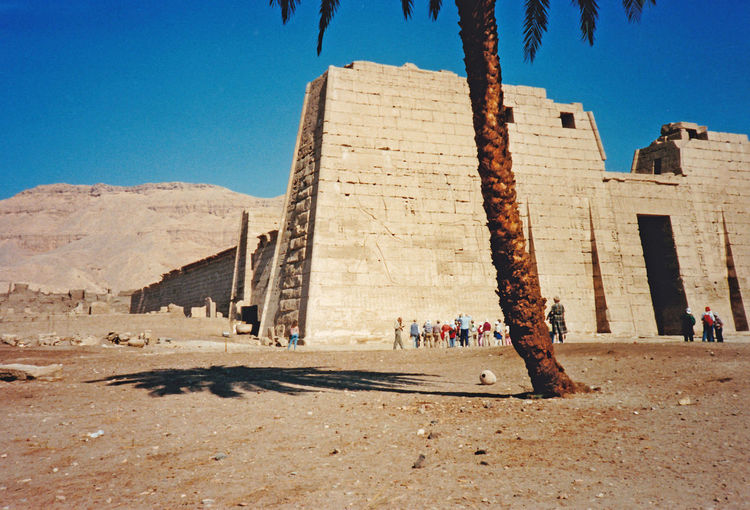 The Mortuary Temple of Ramesses III at Medinet Habu - Valley of the Kings, Thebes, Luxor, Egypt Architecture Nature Sky Blue Shadow Sunlight Day History Outdoors Ancient Pyramid Clear Sky Valley Of The Kings No People Palm Trees ❤❤ Travel Destinations Low Angle View Ancient Civilization Building Exterior Built Structure Old Ruin Medinet Habu First Pylon Egyptian Temples