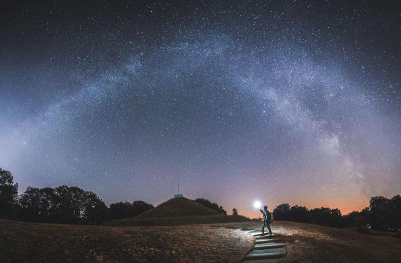 Man holding flashlight on land against sky