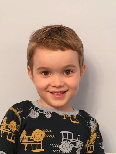 Portrait of smiling boy standing against wall
