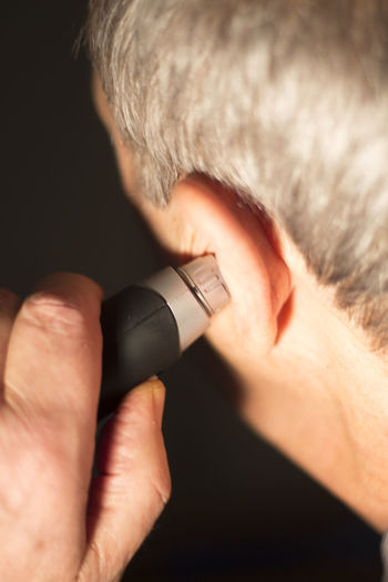 Close-up of man holding electric razor to ear