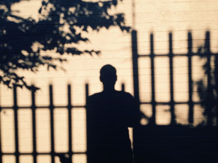 Rear View Of A Silhouette Man Against Wall