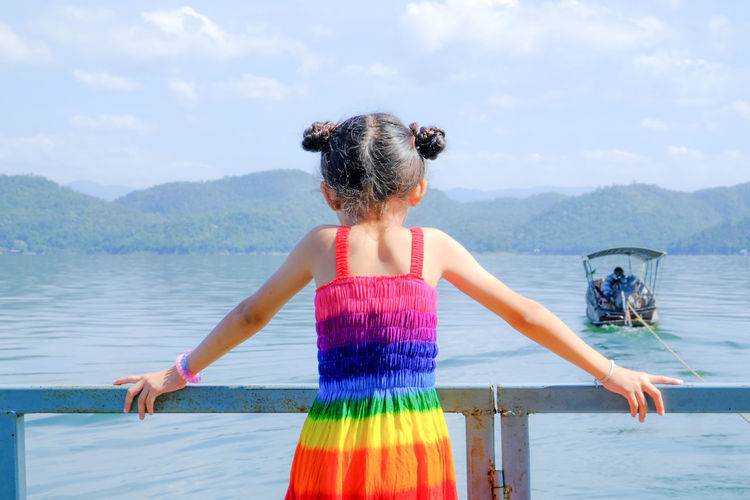 Adult Beauty In Nature Child Childhood Day Girls Hairstyle Human Arm Leisure Activity Lifestyles Nature One Person Outdoors Real People Rear View Sea Sky Standing Three Quarter Length Water Women