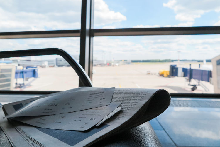 newspaper and tickets lying on a chair at the airport Transportation Mode Of Transportation Window Transparent Focus On Foreground Book No People Day Indoors  Glass - Material Publication Cloud - Sky Paper Close-up Travel Vehicle Interior Sky Air Vehicle Table The Traveler - 2019 EyeEm Awards My Best Photo
