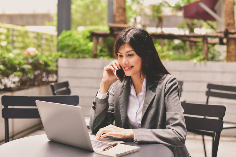 Adult Business Businesswoman Communication Computer Connection Focus On Foreground Laptop Mobile Phone One Person Outdoors Portable Information Device Real People Seat Sitting Table Technology Telephone Using Laptop Wireless Technology Women