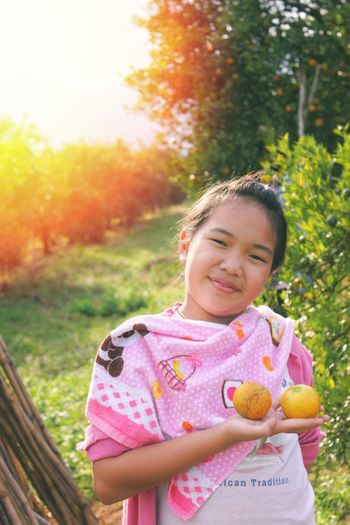Portrait of smiling girl holding fruits while standing at farm