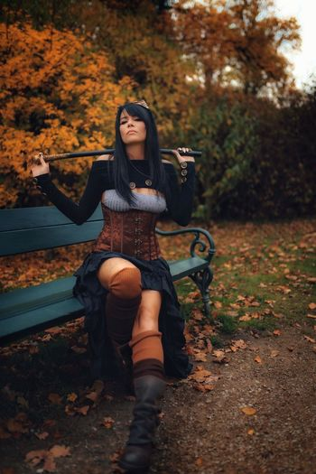 Full length of young steampunk woman sitting on bench
