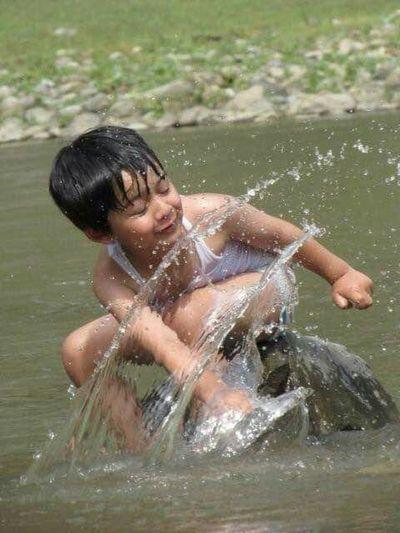 Boy splashing water while sitting on rock in river