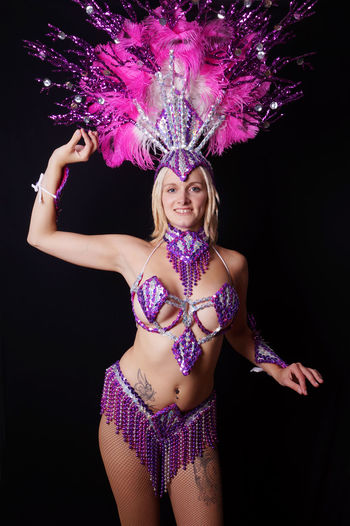 Alternative Black Background Costume Dance Dancer Dancing Girl Glamour Happy Headpiece Inked People Pink Purple Real People Samba Skimpy Smiling Studio Shot Tattooed Woman Women Young Adult Young Woman