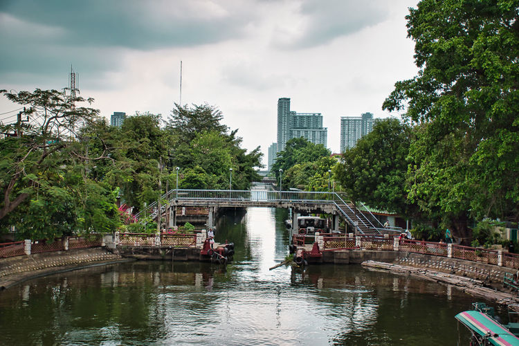 Bridge over river in city against sky