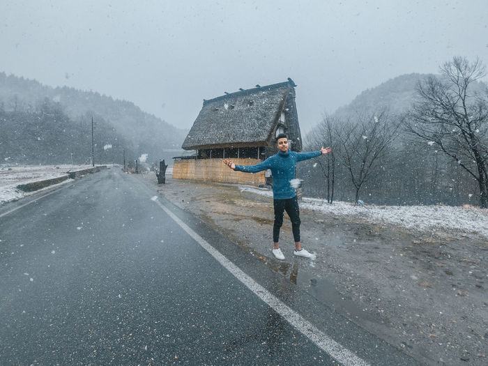 Portrait of man with arms outstretched standing on road during winter