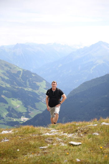 Portrait of male hiker walking on mountain against cloudy sky