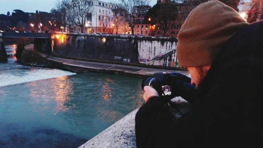 Midsection of woman photographing river in illuminated city during winter