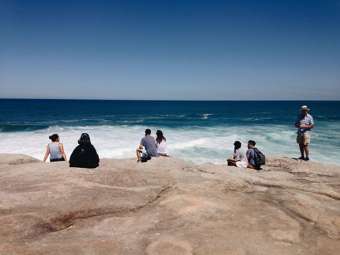 Rear view of people sitting on rocks at beach against clear sky during summer