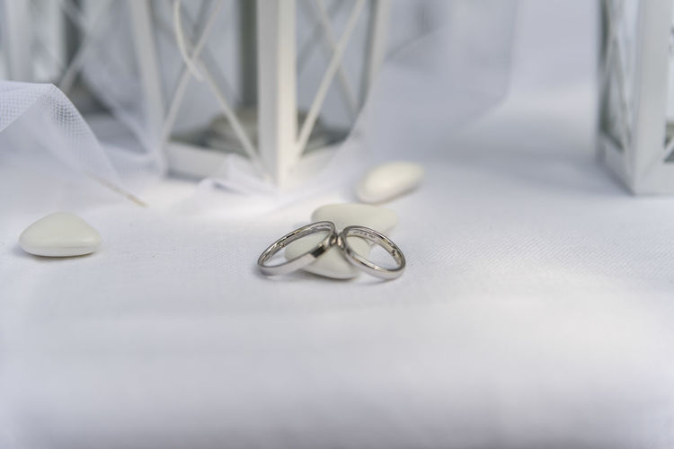 Close up of Wedding rings near comfits and wedding favors Indoors  No People Still Life Event Celebration White Color Wedding Close-up Jewelry Wedding Ring Table Selective Focus Ring Life Events Textile Metal Eyeglasses  Emotion Paper Glasses Silver Colored Personal Accessory Small Group Of Objects