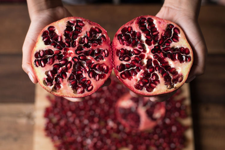 hand holding pomegranate Agriculture Medicine Close-up Cross Section Day Focus On Foreground Food Food And Drink Fresh Freshness Fruit Healthy Eating Healthy Lifestyle Holding Human Body Part Human Hand Indoors  Lifestyles Peeled People Pomegranate Pomegranate Seed Real People Red Seed